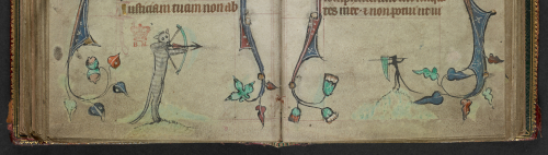 An opening from a Book of Hours, featuring a marginal illustration of a cat with a bow and a mouse lancer taking aim at each other.
