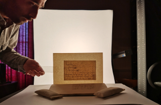 Photograph showing the transmitted light technique for the digitisation of a Newman manuscript