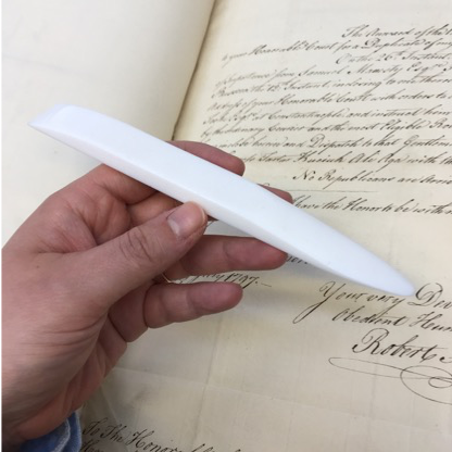 A hand is holding a white teflon bone-folder. In the background there is an 18th century manuscript.