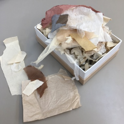 A small box overflowing with different types of scrap pieces of Japanese repair tissue. The tissues differs in thickness, colour and texture.