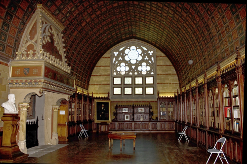 A photograph of the Salle de la Diana, showcasing a vaulted ceiling, adorned with coats of arms and its walls lined with bookshelves, with a stone fireplace on the left-hand side.