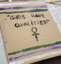 "Cardboard banner saying ""Girls have qualities!"""