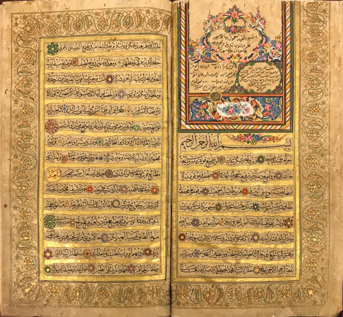 Double page of text in Arabic script surrounded by intricate gold floral illumination and gold borders. At the top right of the image is copious floral illustration in red, blue, green, white, black, purple, pink and gold inks.