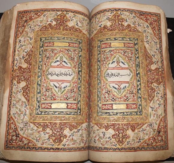 Central pages of a Qur'an manuscript from Java, marking the start of a Surat al-Kahf, enclosing a single line of text on each page. National Library of Singapore, Farish Noor Collection.