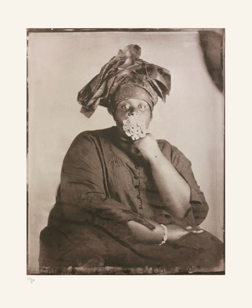 Khadija Saye, facing the camera, holds a large bunch of cowrie shells in her mouth