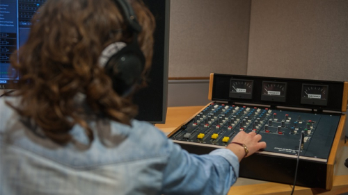 A woman controls the sound levels of a recording using an analogue mixing desk
