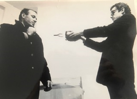 Black and white photo of Guy Brett standing upright and holding a magnet towards Takis who is also standing upright