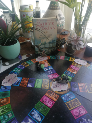 A boardgame on a table with a paper ship at the centre of the board, and pot plants behind it