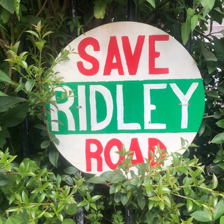 Photograph of a red, white and green sign surrounded by leaves