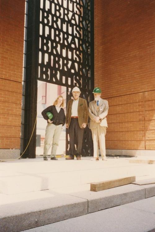 Lida Kindersley, architect Sir Colin Alexander St John (Sandy) Wilson and David Kindersley in front of the British Library gates