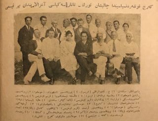 A reproduction of a black and white photograph of a group of 18 people including 2 women and 16 men, of whom 7 are seated in a front row, 9 are standing behind them, and a further two are standing behind that row, all of them in various forms of business or casual attire, with a bolded title in Arabic script above the photo and an Arabic-script caption below it