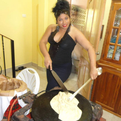 Photography of woman holding utensils while she cooks roti bread on a hotplate