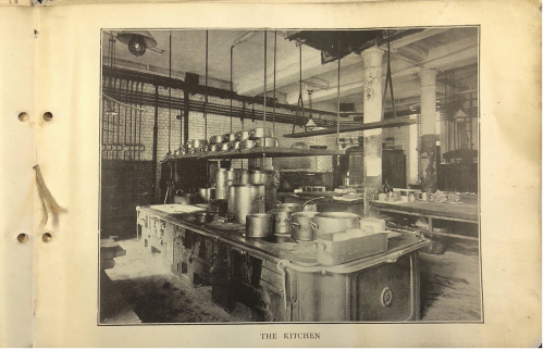 Black and white photograph of kitchen at the Savoy, with pots piled high