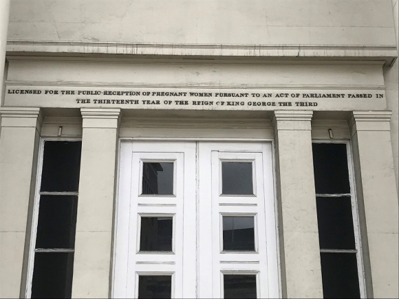 Photo taken 2021 of an inscription over the door of Lying-In Hospital Lambeth - licensed for the reception of pregnant women in the reign of George III
