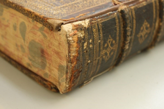 A close-up of the bottom of a spine of one of the volumes showing wear and tear.