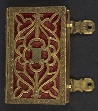 Girdle book shown closed with elaborate metal openwork cover over red velvet