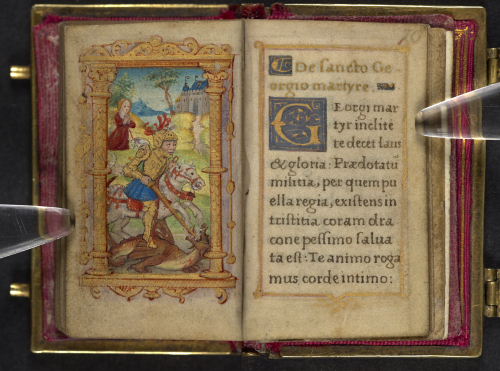 Girdle book held open on the page with a picture of St George slaying the dragon facing a prayer