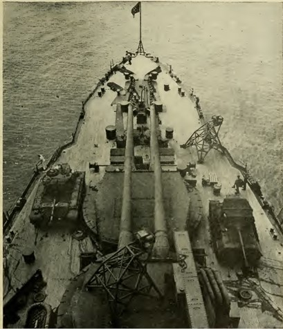 Bow of a battleship with tanks and other equipment parked on it.