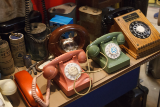 A collection of historic telephone equipment on a table
