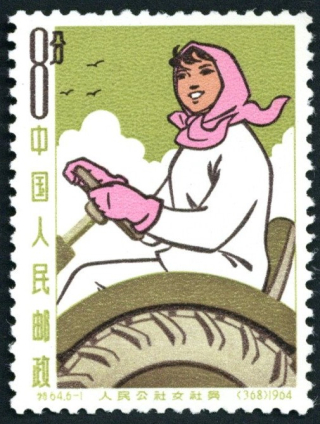 A postage stamp featuring a woman riding a tractor in close-up. The woman is in white with a pink handkerchief on her head, and the tractor and background are light green