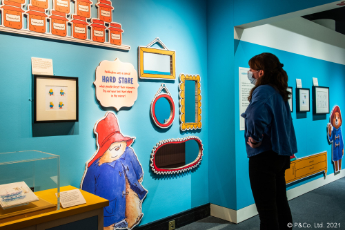 A woman in a face-mask stands in front of a cut-out of Paddington bear in the British Library exhibition, Paddington: The Story of a Bear