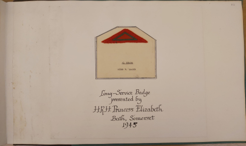 Triangular red long service badge pasted into the diary, presented by HRH Princess Elizabeth, 1945