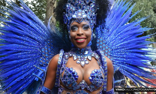 Paraiso School of Samba dancer at the Notting Hill Carnival 2018, © Vinko Kalčić Photography, reproduced with permission. Image shows a close-up portrait of a smiling dancer of the Paraíso School of Samba. The dancer wears a dress made of blue coloured gems and feathers