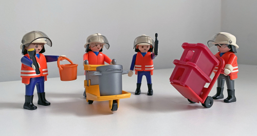 Four Playmobil figures, wearing personal protective equipment, are shown using emergency response equipment