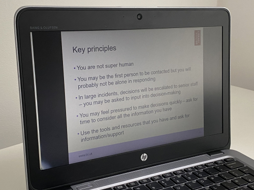 A slide from a decision-making training presentation, which outlines key principles, is displayed on laptop screen