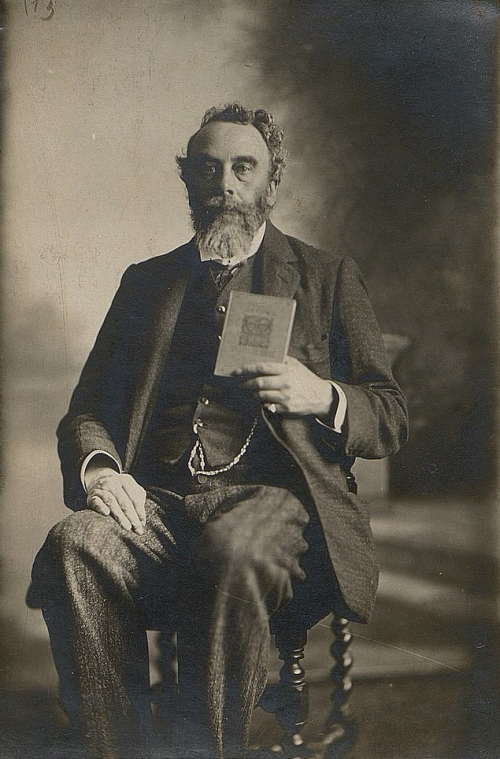 Portrait of Edward Spencer Dodgson sitting in a chair and holding a book