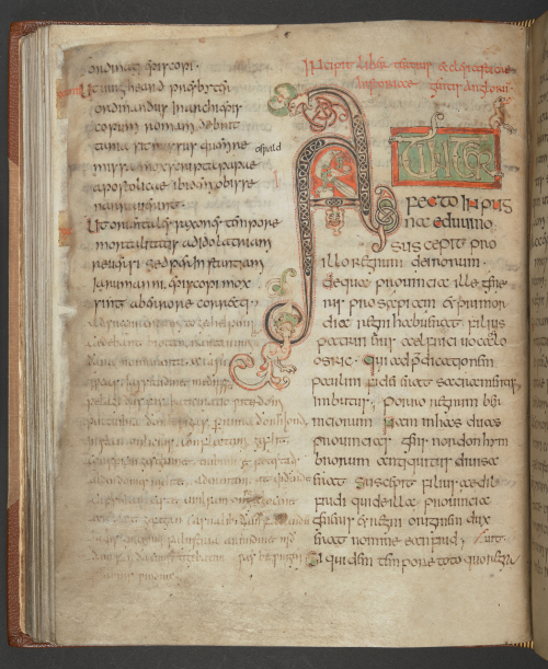 Manuscript page in two columns with large decorated initial A in black, red, and green ink.
