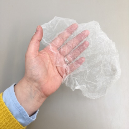 A hand holds a very fine piece of Japanese tissue. It is so thin and delicate that the hand is fully visible through the matrix of the tissue.