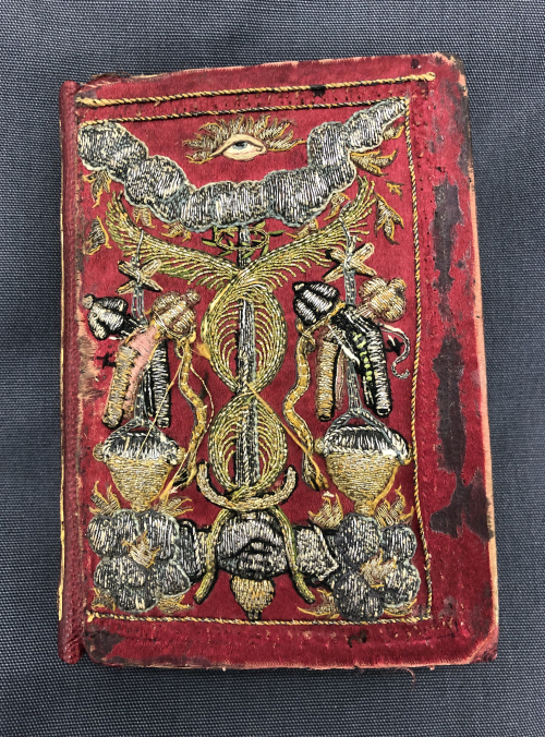 The upper cover of the autograph manuscript of Loÿs Papon's Pastorelle, featuring a red velvet cover, with a number of symbols embroidered in silver, gold, and coloured thread.