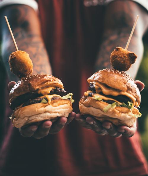 Two cheeseburgers being held