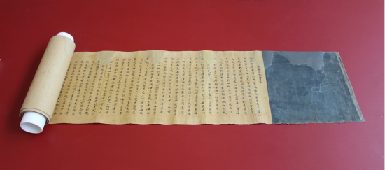 Scroll after treatment with no tears or missing areas, laid out on a red table.