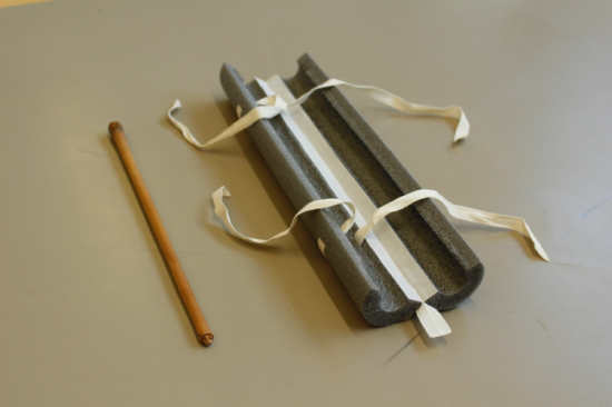 The foam tube which houses the detached original rod with the scroll. This tube is split open showing how the tape is threaded through small slits in the tube.