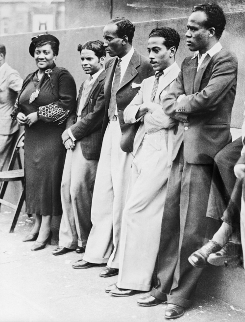 Black and white photograph of one woman and four men standing next to each other in front of a short wall; all are smartly dressed.