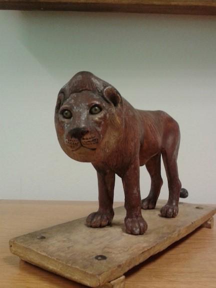Model of a lion standing on a wooden base a halter round his neck Gangaram Cintamani Tambat