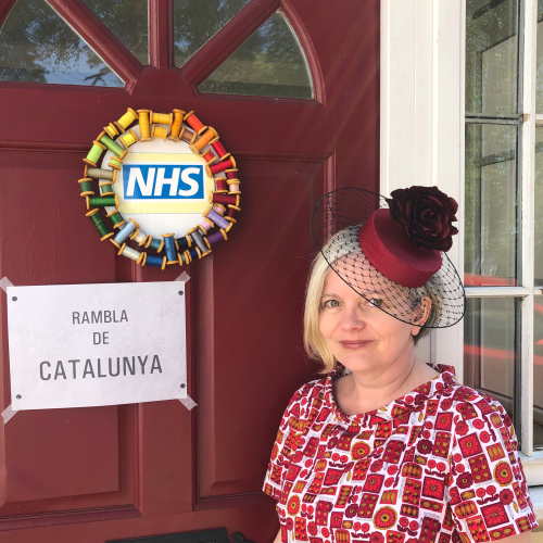 Susan wearing one of her designs in front of an NHS wreath made from sewing thread