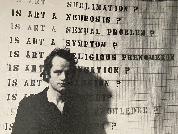 Black and white photo of Guy Brett in front of an art work which is a series of written questions each beginning with 'Is Art?'