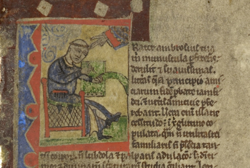 A blue and red initial with a tonsured figure in a dark blue habit seated at a writing desk, holding a scroll in one hand and a quill in the other
