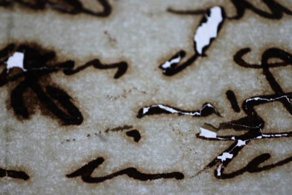 Figure 2: A magnified image of iron gall ink on paper, lit from the back, showing dark haloing around the text and areas of loss from regions of heavy ink.