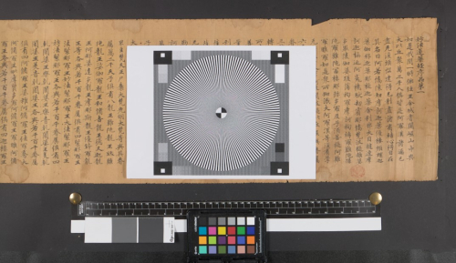 Black background behind a yellowed scroll with Chinese characters on it and a black and white focus target with a multicoloured colour palette and black and white strips at bottom of image