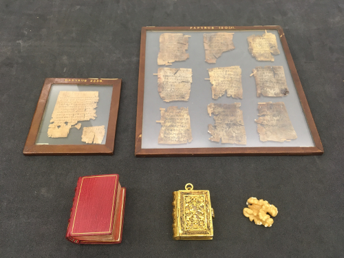 A papyrus leaf, a frame containing nine parchment leaves, a book in a red binding, a book in a gold binding, and a walnut
