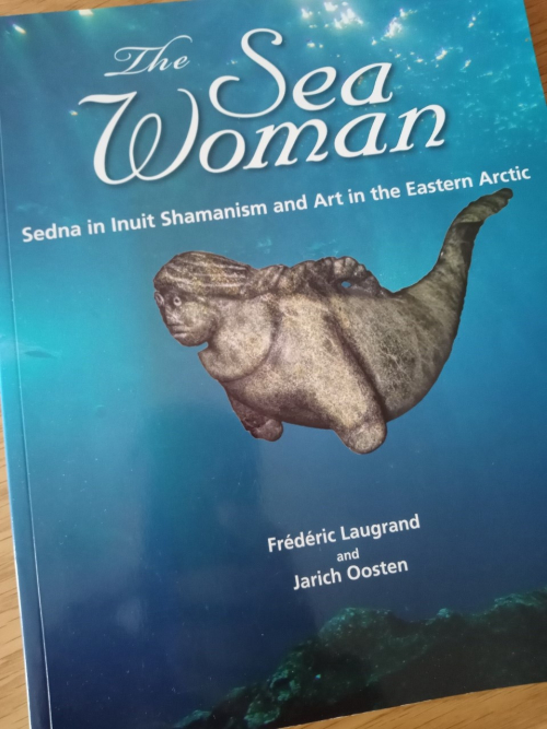 The cover of Frédéric Laugrand and Jarich Oosten's The Sea Woman: Sedna in Inuit Shamanism and Art in the Eastern Arctic, showing the mermaid-like goddess in blue water.