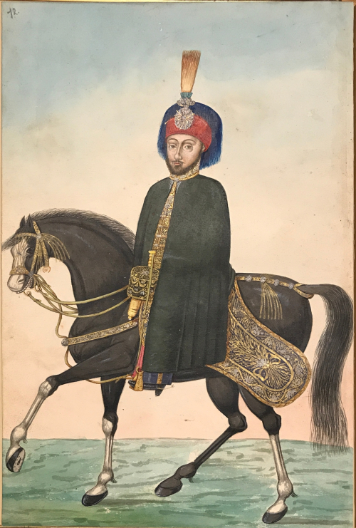 Full-page painting of a man mounted upon a cantering black horse with white legs, atop of an ornate saddle, wearing a black cape and red fez topped with a lavish standard. The man is bearded and looking at the viewer