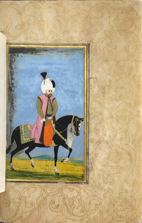 A painting of a middle-aged man in a green tunic with a white turban and black tassel upon his head sitting atop a black horse. The man is bearded and the horse is covered in a richly decorated saddle. The image is set within a page that features gold-wash illuminations in floral patterns