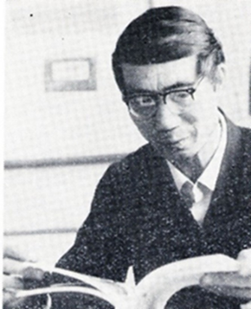A black and white photograph of a man in glasses, from the waist up. He is reading a newspaper while wearing a black suit and glasses.
