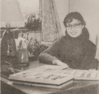 A black and white photograph of a woman seated at a desk, looking into the camera. Her hair is in pig-tails and she is wearing a jumper and glasses.