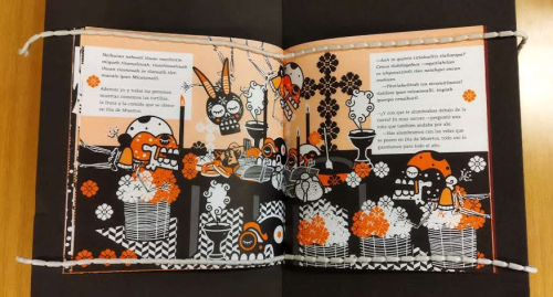 An open book. In both pages and illustration in two colours, black and orange, depicting a Day of the Dead Altar with a table with food, bread, candles, decorated sugar skulls, flowers and incense burns. Four skeletons are flying around the table smelling the content of the altar.